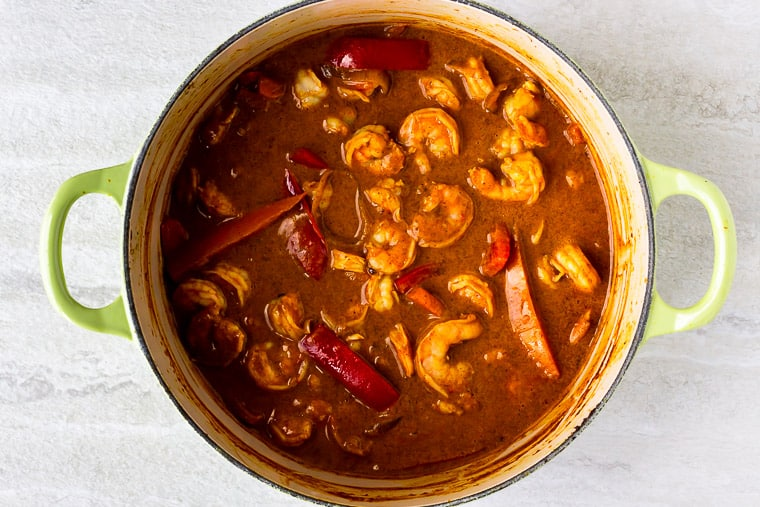 Shrimp in a coconut curry sauce with peppers in a Dutch oven over a white background