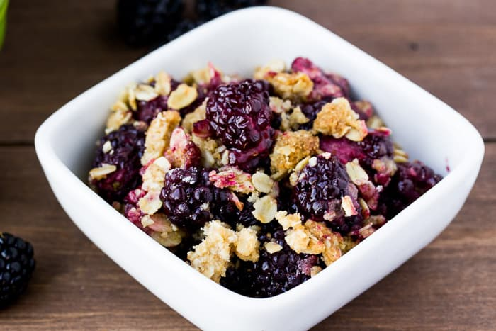 Blackberry Crisp in a White Dish on a wood background