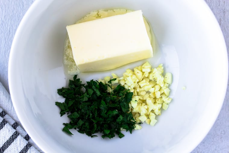 half a stick of butter, minced garlic and minced parsley in a white bowl over a white background