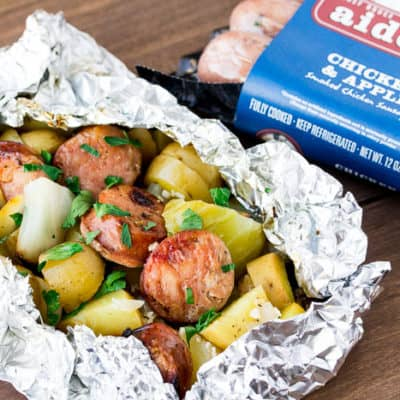 Grilled Sausage Foil Packets with Cabbage and Potatoes with a Package of Sausage on a Wood Back Drop