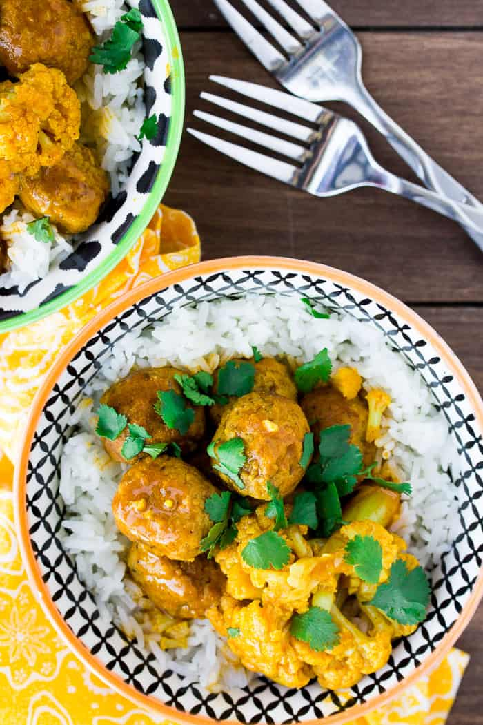 2 Bowls of Instant Pot Coconut Curry Meatballs & Cauliflower with 2 Forks on a Wooden Board