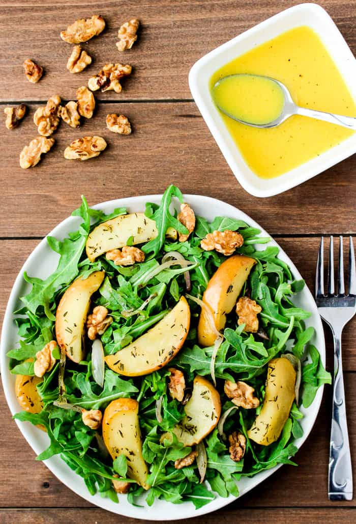 Roasted Apple Arugula Salad on a White Plate with Dressing in a white square bowl with a spoon, extra Walnuts, and a fork all on a wood background