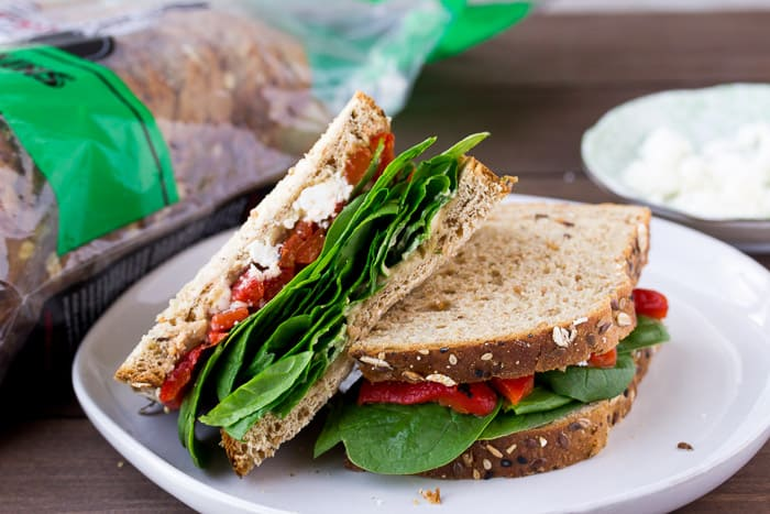 A Roasted Red Pepper Spinach Sandwich Cut in Half on a White Plate