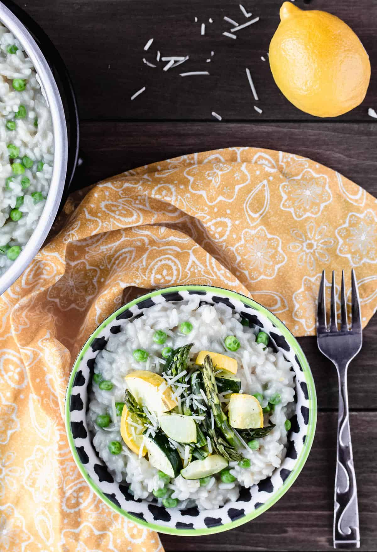 overhead of a bowl of spring vegetable risotto with a yellow towel, fork and lemon around it on a wood background
