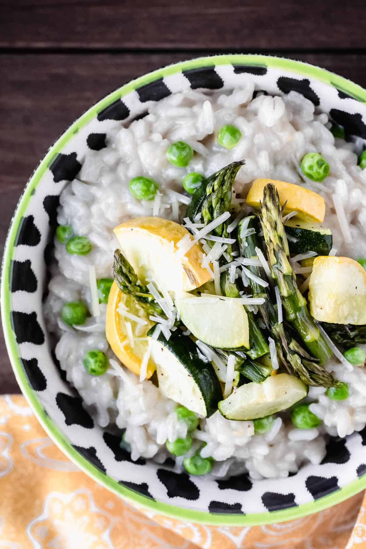 CLose up of spring vegetable risotto in a black, white and green bowl over a wood background with a yellow towel partially showing