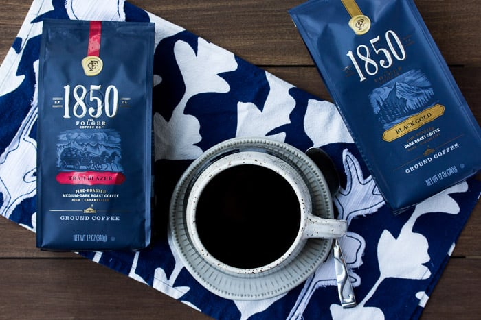2 Packages of 185- Brand Coffee with a Cup of Coffee on a Blue Napkin