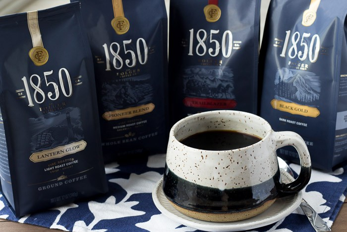 4 Packages of 185- Brand Coffee with a Cup of Coffee on a Blue and White Napkin