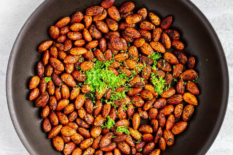 Chili almonds with lime zest in a skillet over a white background