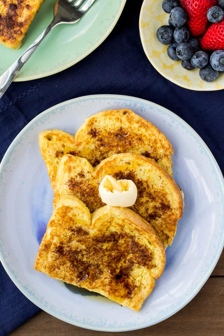 overhead view of 3 slices of Vanilla Cinnamon French Toast on a Blue Plate with a Blue Napkin and Berries and part of another plate of french toast on a wood backdrop