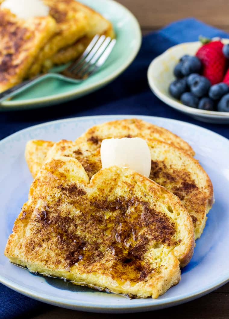 Vanilla Cinnamon French Toast on a Blue Plate with a second plate and Berries in the Background on a wood background
