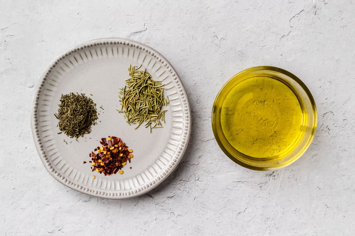 Ingredients for bread dipping oil with dried herbs on a white background