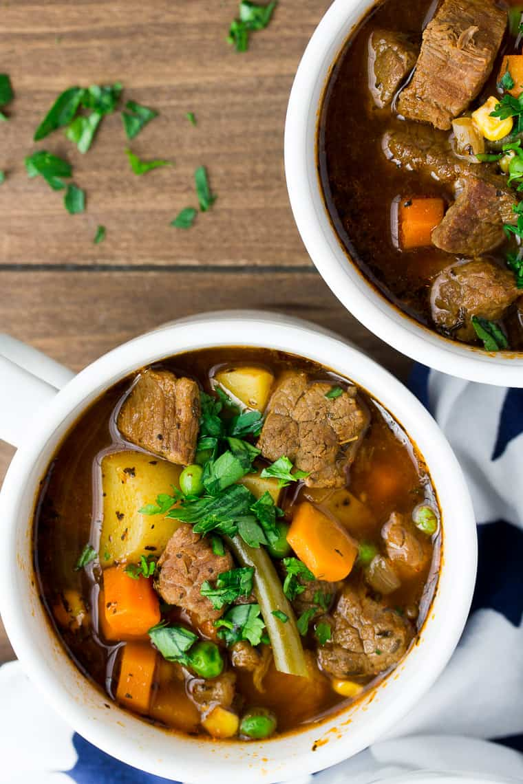 2 Bowls of Instant Pot Vegetable Beef Soup in White Bowls over a wood background with extra fresh herbs spread around