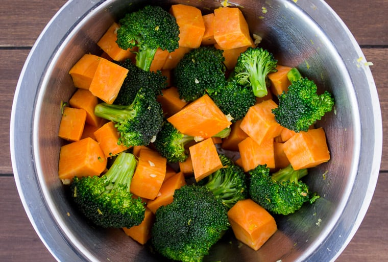 Cubed sweet potatoes, broccoli, lemon zest, and garlic mixed together in a silver bowl