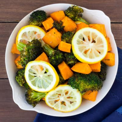 Overhead view of lemon roasted broccoli and sweet potatoes in a white serving dish on a wood backdrop with a blue napkin