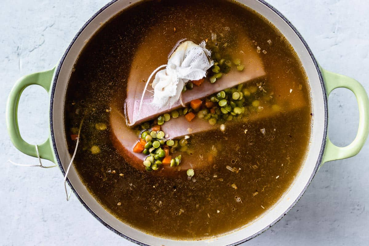 Split pea ham soup cooking in a Dutch oven over a white background