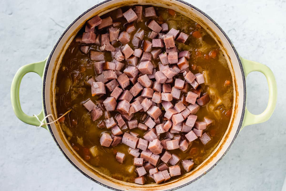 Diced ham added to split pea ham soup in a Dutch oven over a white background