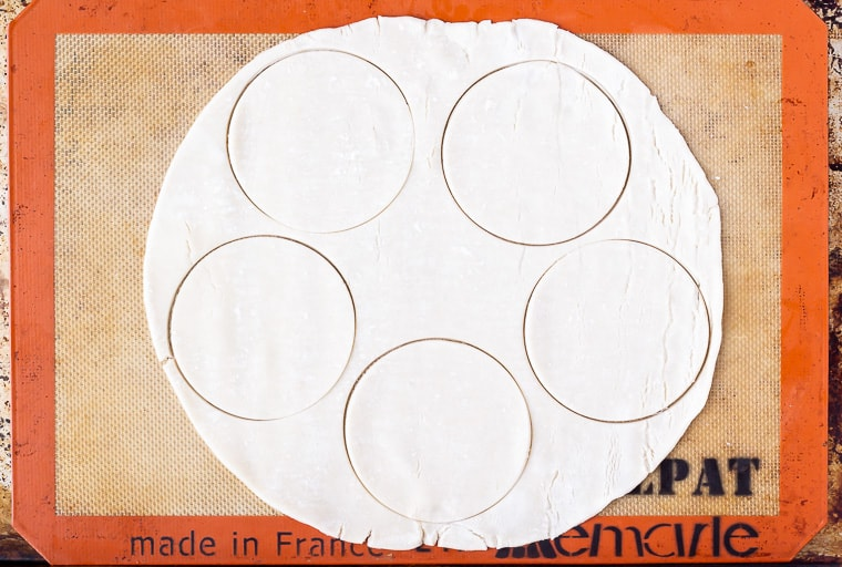 A pie crust with 5 mini pies crusts cut into it on a silpat mat
