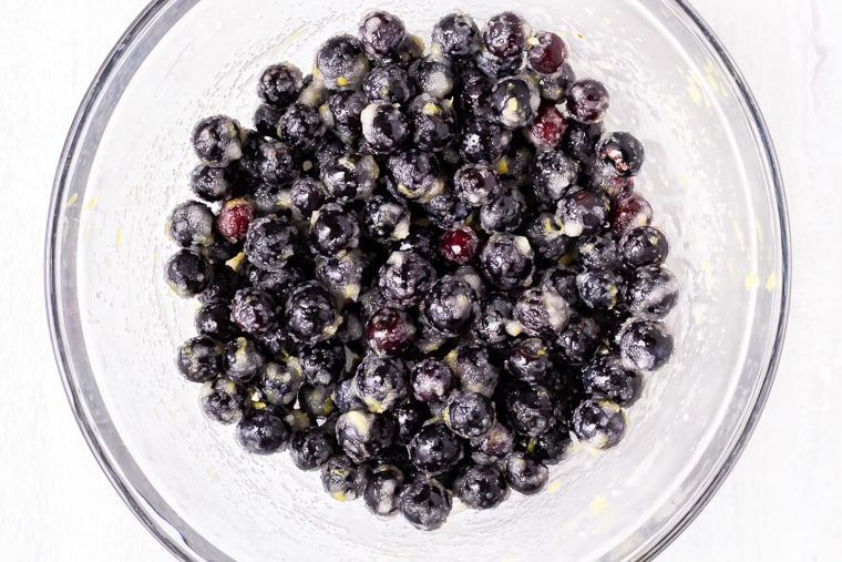 Sugared blueberries in a glass bowl over a white background