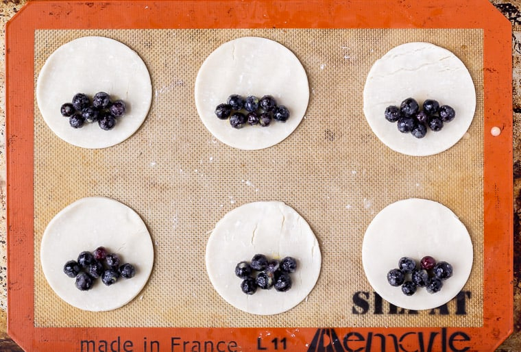 6 mini pie crusts with blueberries on one half of each on a silpat baking mat