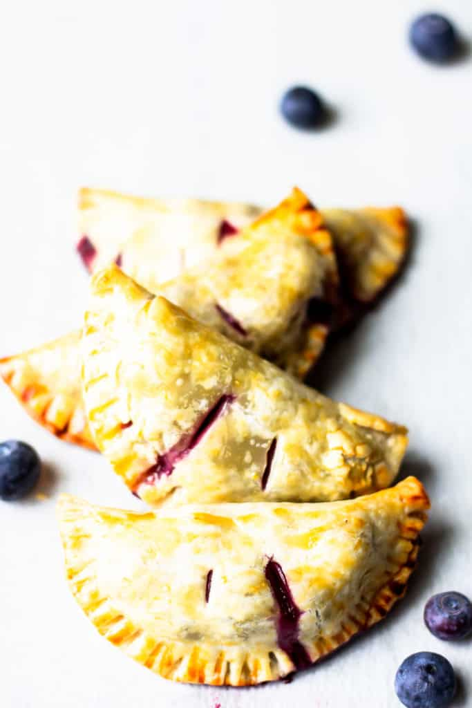 4 blueberry hand pies in a line back over a white board with a few fresh blueberries around them