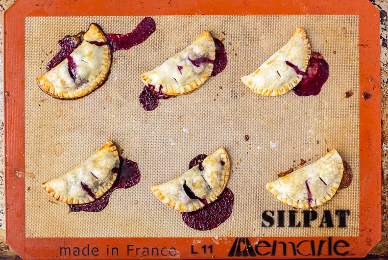 Baked mini blueberry hand pies with juices leaking out onto a silpat mat
