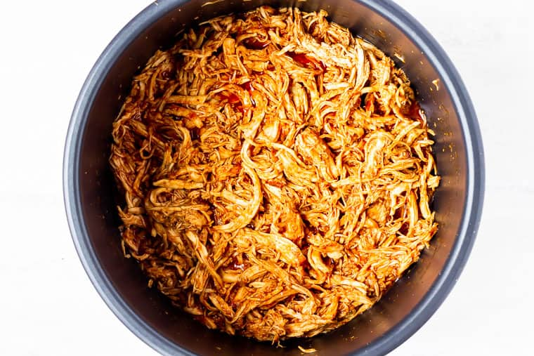 Shredded chipotle chicken in an instant pot over a white background