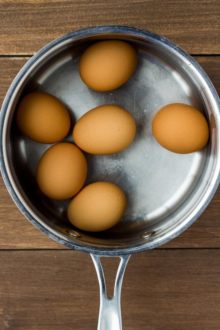 6 Brown Eggs in a Saucepan Covered in Water over a wood background