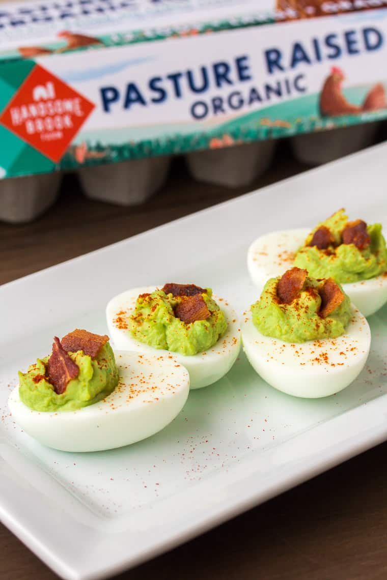 Bacon Avocado Deviled Eggs on a White Plate with Egg Carton in the Background