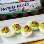 Bacon Avocado Deviled Eggs on a White Serving Tray with an Egg Carton and Avocado in the Background