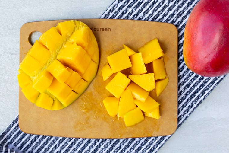 Mango half and chunkson a cutting board with a blue/white strip napkin and whole mango in the background on a white backdrop