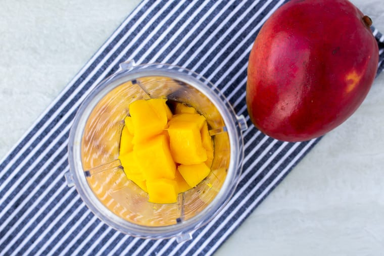 Mango and other ingredients in a blender cut on a blue/white striped napkin and a whole mango over a white background