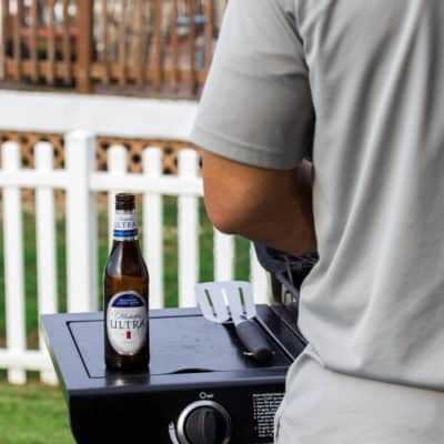 Man Cooking on the Grill with Michelob ULTRA Bottle Next to Him for Father's Day