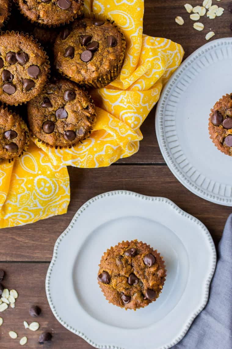 Pumpkin Chocolate Chip Muffins in a Bowl with a Yellow Napkin and 2 Muffins on White Plates.