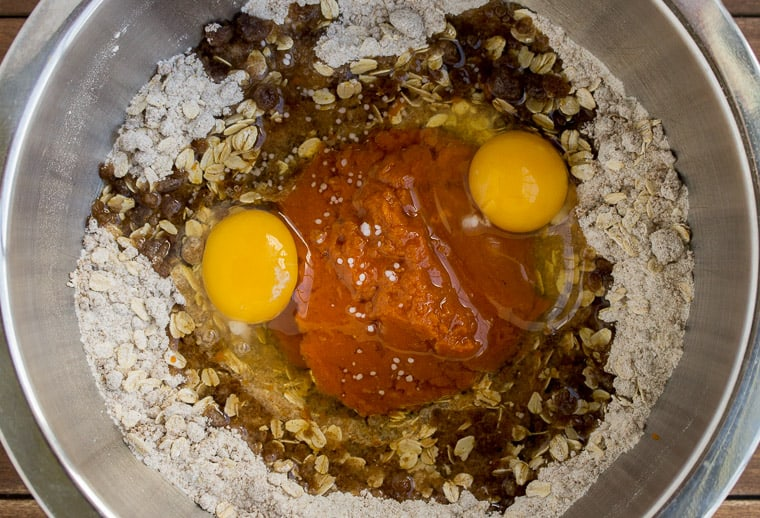 Pumpkin, Eggs, and Oil in the Middle of the Dry Ingredients in a Silver Bowl