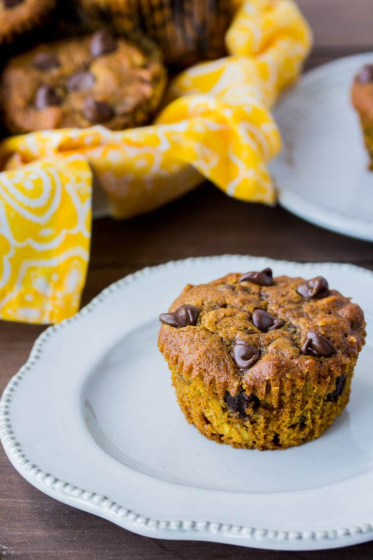 A Pumpkin Spice Chocolate Chip Muffin on a White Plate on a Wood Back Drop