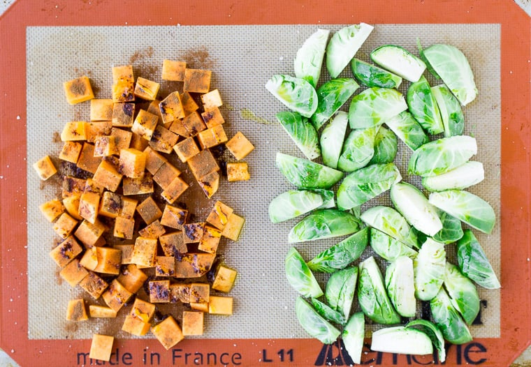 Cubed Butternut Squash and Brussels Sprouts on a Baking Sheet with Seasoning