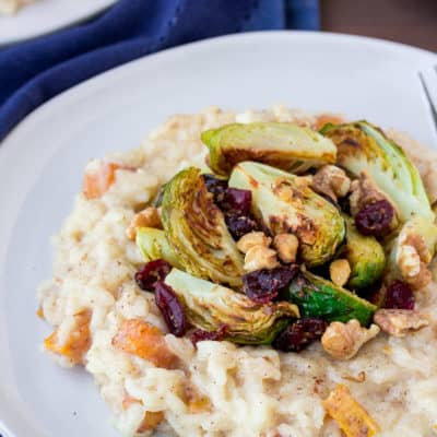 Roasted Butternut Squash Risotto with Brussels Sprouts, Cranberries, and Walnut on a Blue Plate with a Blue Napkin