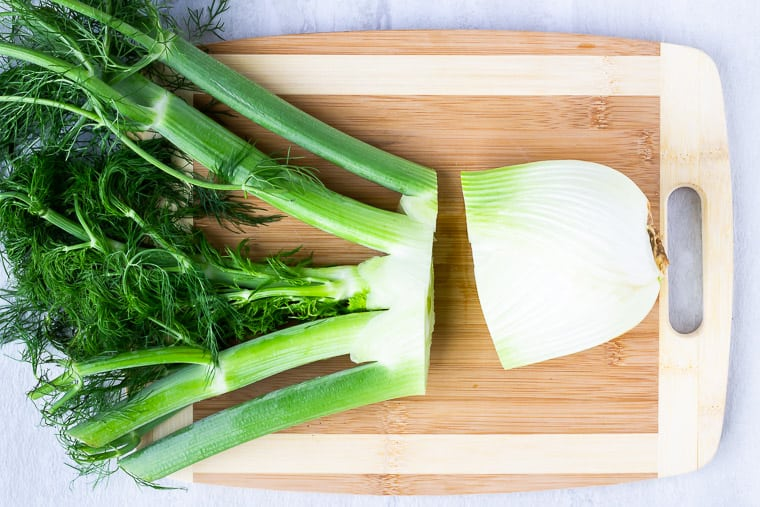 Fennel on a wood cutting board with the stalks cut off of the bulb