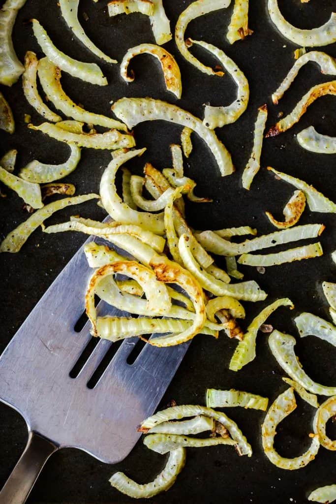 Close up of roasted fennel on a silver spatula on a baking sheet