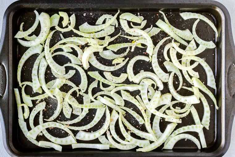Raw fennel slices on a baking sheet seasoned with olive oil, salt and pepper