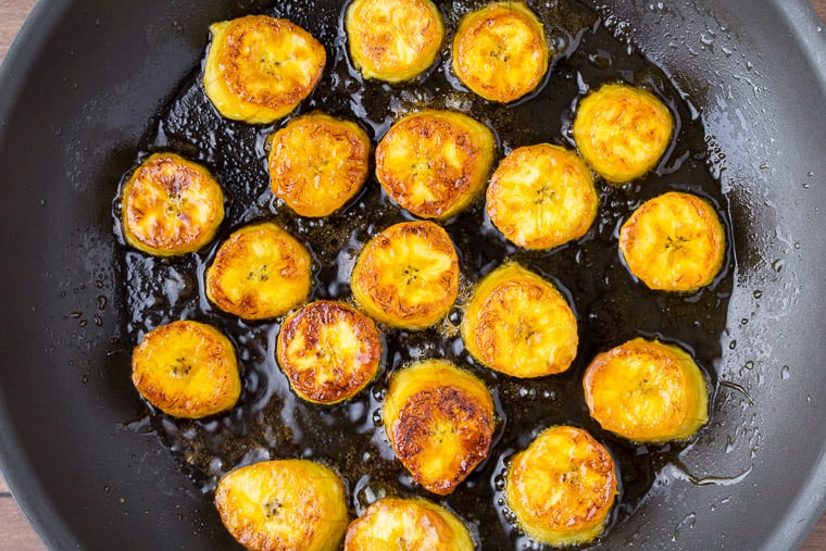 Browned Plantains Cooking in oil in a Black Skillet