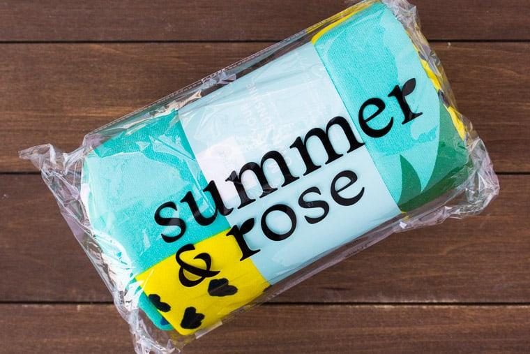 Summer & Rose Beach Towel in Packaging on a Wood Back Drop