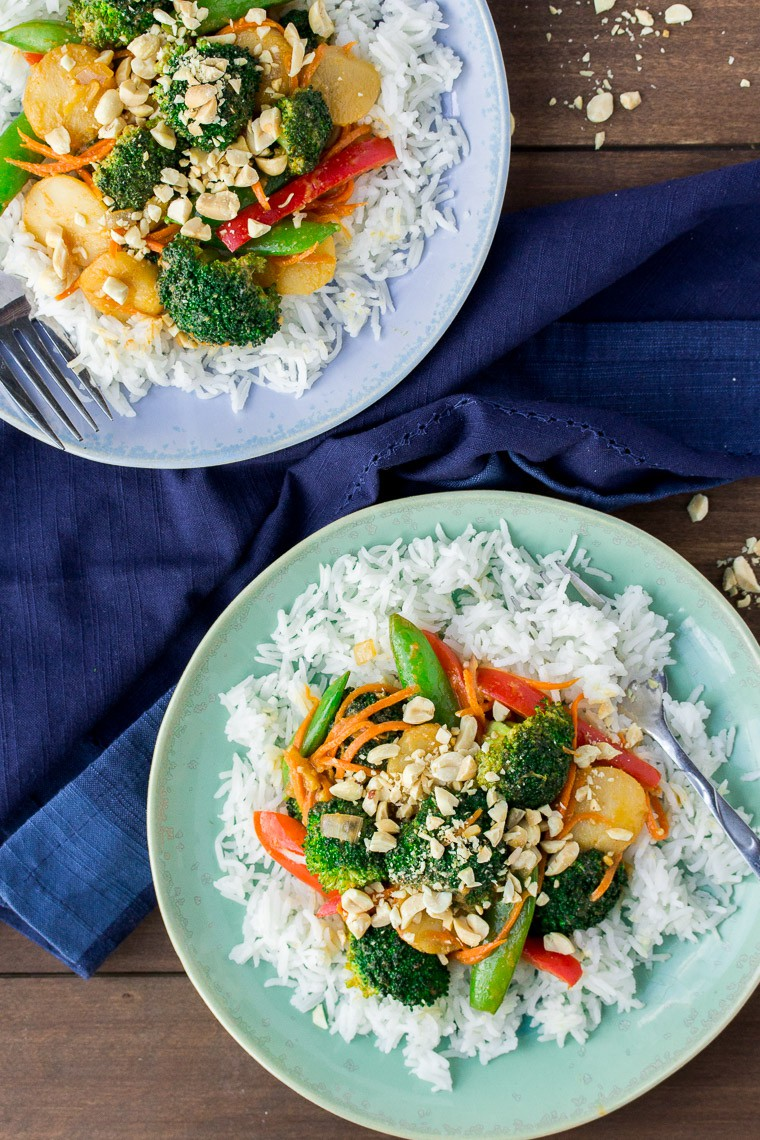 Vegetable Peanut Stir Fry on 2 Blue Plates with a Blue Napkin on a Wood Backdrop
