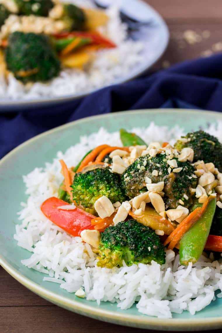 Vegetable Stir Fry on 2 Plates with a Blue Napkin on a Wood Backdrop