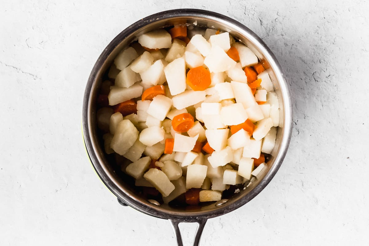 Potatoes and carrots in a small pot over a white background