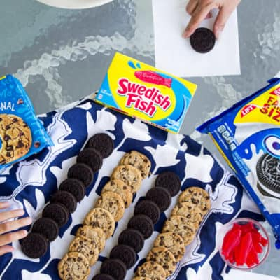 Chips Ahoy, Oreos, ans Swedish Fish Set Out for Snacking with Two Hands Reaching for Cookies