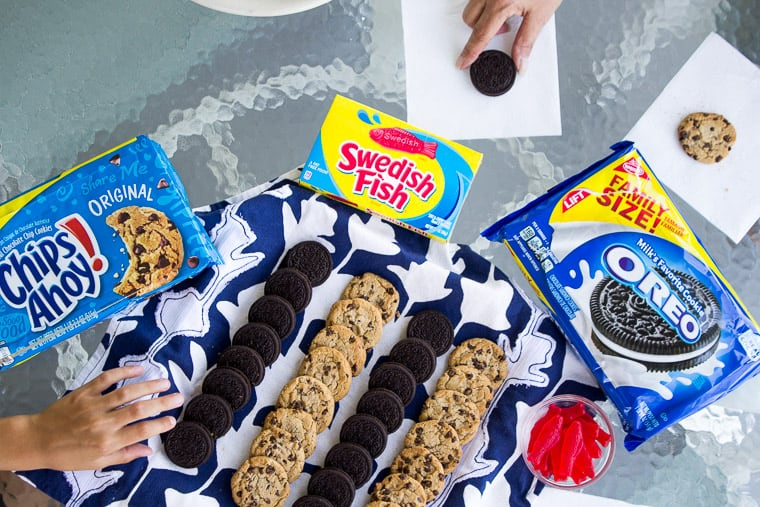 Chips Ahoy, Oreos, ans Swedish Fish Set Out for Summer Snacking with Two Hands Reaching for Cookies