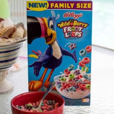 Wild Berry Froot Loops Box with a Bowl of Cereal on a Table Outside with a Pool in the Background