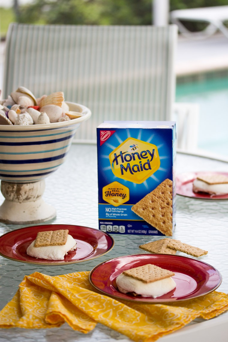 Honey Maid Grahams Box on a Table with Red Plates with S'mores on Them with a Chair and Pool in the Background