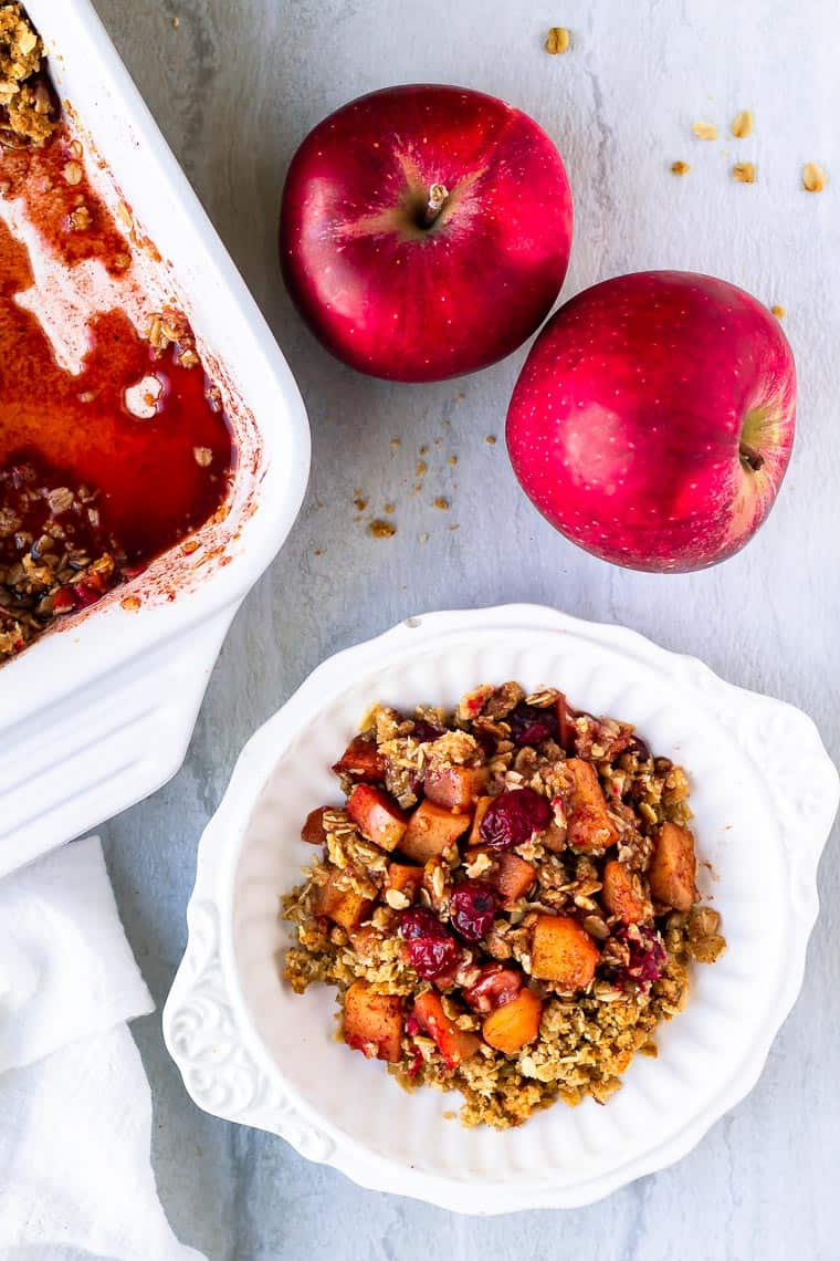 Overhead of Cranberry Apple Crisp in a white bowl with 2 apples, some crumbs and part of the white casserole dish in the background